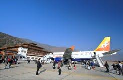 有行李的人走和拍摄照片的在Paro机场在登陆以后 免版税库存照片