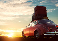 有行李的减速火箭的红色汽车在日落的行李架 旅行,假期概念 库存图片