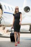 有行李的妇女走反对私人喷气式飞机的 免版税库存图片