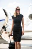 有行李的富有的妇女走反对私有的 库存图片