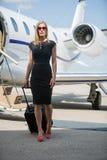 有行李的富裕的妇女走反对私有的 库存照片