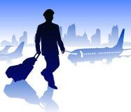 有行李的航空公司飞行员在反对城市的机场 免版税库存照片