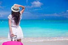 有行李的年轻美丽的女孩在海滩期间 库存图片