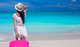 有行李的年轻美丽的女孩在海滩期间 免版税图库摄影