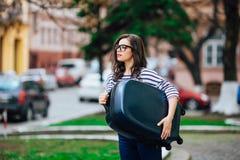 有行李走的城市街道的女孩 图库摄影