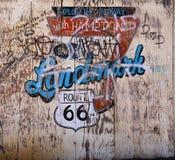 有街道画的老困厄的胶合板标志路线66 库存照片