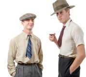 有衣裳和盖帽的两个年轻人在30s样式 库存照片