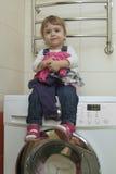 有衣裳的愉快的逗人喜爱的小女孩坐在家庭内部的洗衣机 库存照片