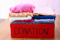 有衣裳的捐赠箱子 一箱温暖的衣裳 免版税库存照片