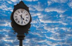 有表明4:30和天空蔚蓝的罗马数字的葡萄酒外部时钟与云彩 库存照片