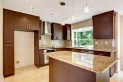 有表面无光泽的棕色内阁和发光的花岗岩的现代厨房室 免版税库存照片