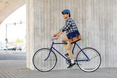 有袋子乘坐的固定的齿轮自行车的年轻行家人 免版税库存图片