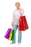有袋子和移动电话的愉快的高级妇女 免版税库存图片