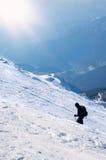 有袋子和鞭子的登山家去一座多雪的山的上面在一个晴朗的冬日 库存照片