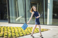 有袋子的典雅的可爱的妇女购物在他的手上在购物中心前面 图库摄影