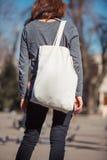 有袋子的女孩在户外他的肩膀 免版税库存图片