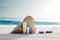 有袋子的帽子在热带海滩 库存图片