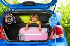 有袋子的愉快的男孩在汽车 免版税库存照片