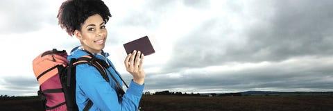 有袋子的旅行的在风景前面的妇女和护照 免版税图库摄影