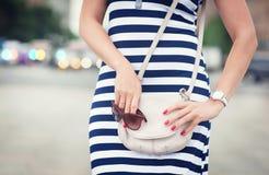 有袋子的时髦的女人在她的手和镶边的礼服上 库存照片