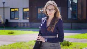 有袋子的确信的女实业家 看照相机和充满信心地走在的成功的年轻女性雇员 股票录像