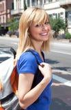 有袋子的笑的白肤金发的学生在城市 免版税库存照片