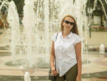 有袋子的美丽的妇女在您的肩膀太阳镜 免版税库存照片