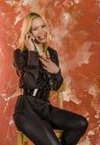 有袋子的美丽的少妇时尚和在一件黑衬衣情感地谈话在电话 图库摄影
