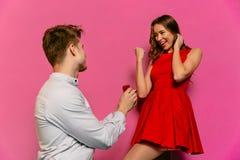 有被举的拳头的美丽的女孩在婚姻的提议以后从她的男朋友的 免版税库存图片