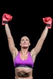 有被举的胳膊的优胜者女性拳击手 免版税库存照片