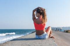 有被举的胳膊的女孩坐沿海岸区,背面图 免版税库存图片