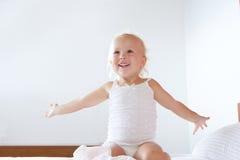 有被举的胳膊的微笑的小女孩 免版税库存图片