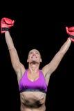 有被举的胳膊的愉快的女性拳击手 库存图片