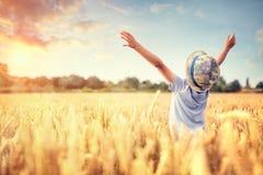 有被举的胳膊的男孩在夏天观看的日落的麦田 免版税库存图片