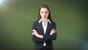 有被交叉的双臂的严肃的女实业家 站立在绿色背景 库存照片