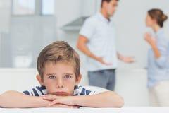 有被交叉的双臂的哀伤的男孩,当争吵时的父母 免版税库存图片
