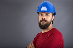 有被交叉的安全帽和双臂的确信的年轻建筑工人 库存照片