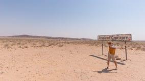 有被伸出的胳膊的一个人在南回归线路标在纳米比亚沙漠,纳米比亚,非洲 库存照片