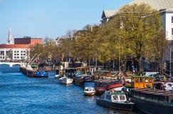 有被停泊的小船的繁忙的Amstel河在阿姆斯特丹 库存图片