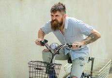 有被刺字的胳膊乘驾自行车的行家 由自行车运输的有胡子的人旅行 有长的胡子的时尚人在剥去 免版税库存图片