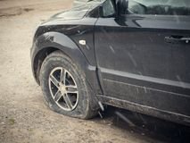有被刺的轮子的黑汽车在露天下 库存照片