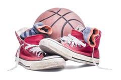 有被剥离的袜子和篮子球的红色运动鞋 免版税库存图片