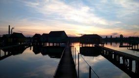 有被反射的日落天空的美丽的湖村庄 库存图片