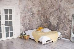 有被回收的板台床的一间顶楼样式卧室 在床上的白色和黄色卧具与在顶楼卧室内部的bedhead 库存图片