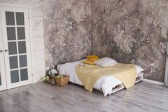 有被回收的板台床的一间顶楼样式卧室 在床上的白色和黄色卧具与在顶楼卧室内部的bedhead 免版税库存图片