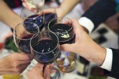 有被填装的杯的男性和女性手在餐馆桌面上的红葡萄酒 饮用的多士和使叮当响的翻转者在fo 免版税库存图片
