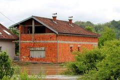 有被填装的窗口的未完成的建筑红砖家庭房子围拢与洪水和密集的森林植物群落 免版税库存照片