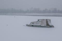有被夺取的小船和海鸥的冻多瑙河 免版税库存图片