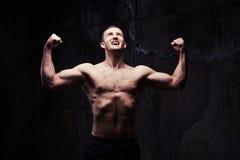 有被定调子的训练的身体的爱好健美者对粗砺的灰色墙壁 图库摄影