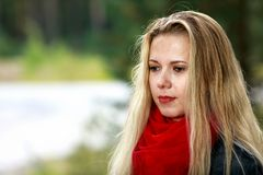 有被弄乱的头发的美丽的哀伤的金发碧眼的女人有在她的脖子的一条红色稀薄的围巾的在被弄脏的b的春天绿叶中站立 免版税库存图片